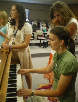 Andrea playing the piano while volunteering at a summer camp for youth.