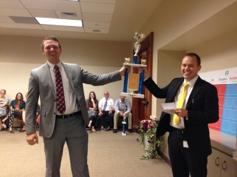 Jake gives out trophies to his employees at their monthly staff meeting